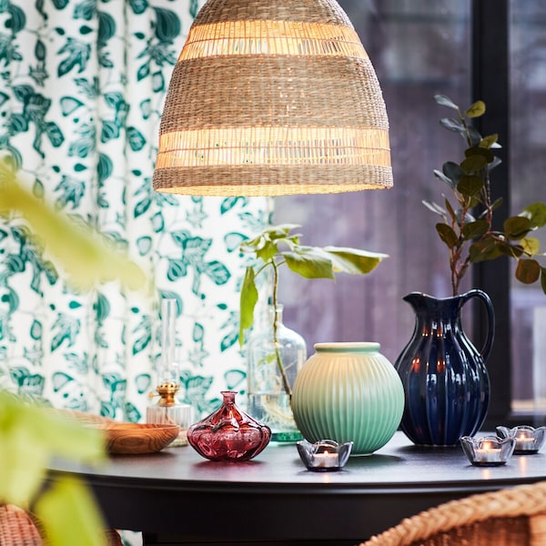 Ein Tisch mit Vasen unter einer Lampe vpr einem grün gemusterten Vorhang.