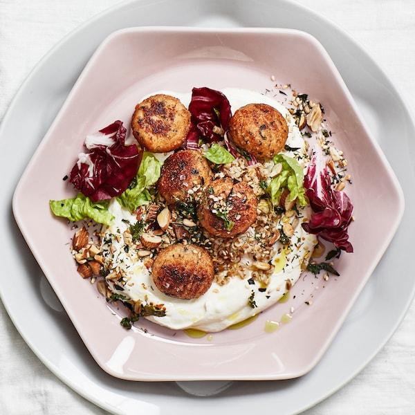 Ein Tisch mit weißer Tischdecke, darauf ein achteckiger Teller mit fünf Fischbällchen auf einem Bett aus Salat, Nüssen und Jogurt.