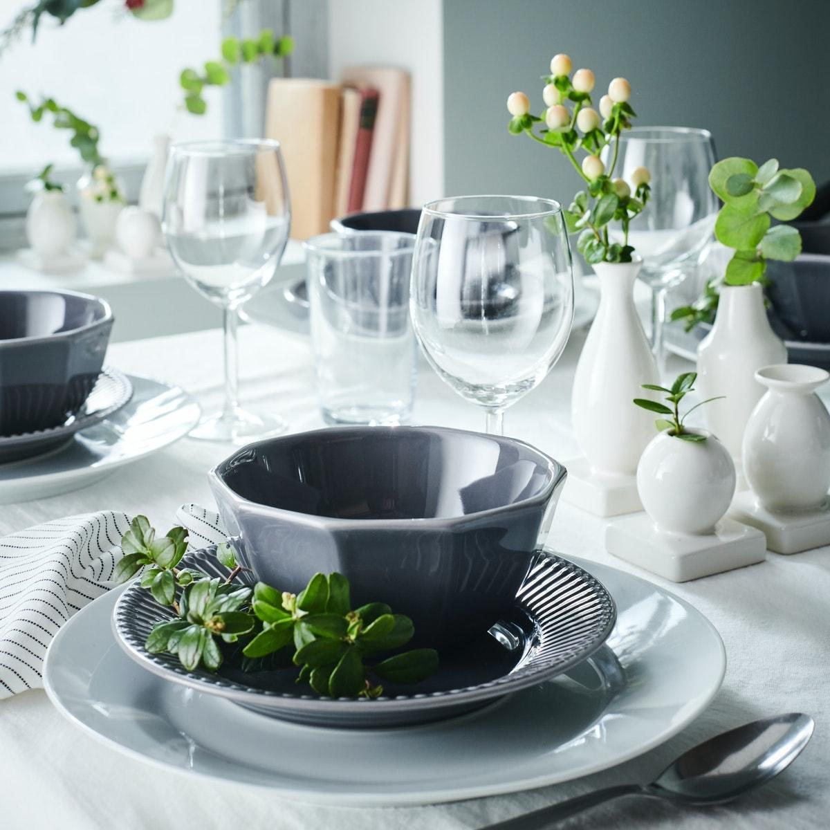 Ein Tischgedeck mit weißen Vasen und grünen Zweigen, kombiniert mit Weingläsern, weißen Tellern und grauen STRIMMIG Schüsseln