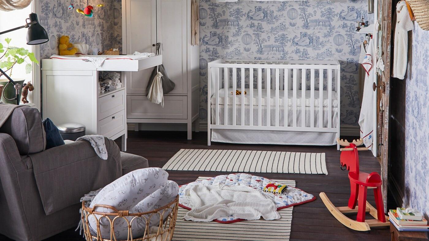 Ein traditionelles Babyzimmer mit weißem Kleiderschrank, Babydecke, Spielbereich, Leseleuchte und Wickeltisch.