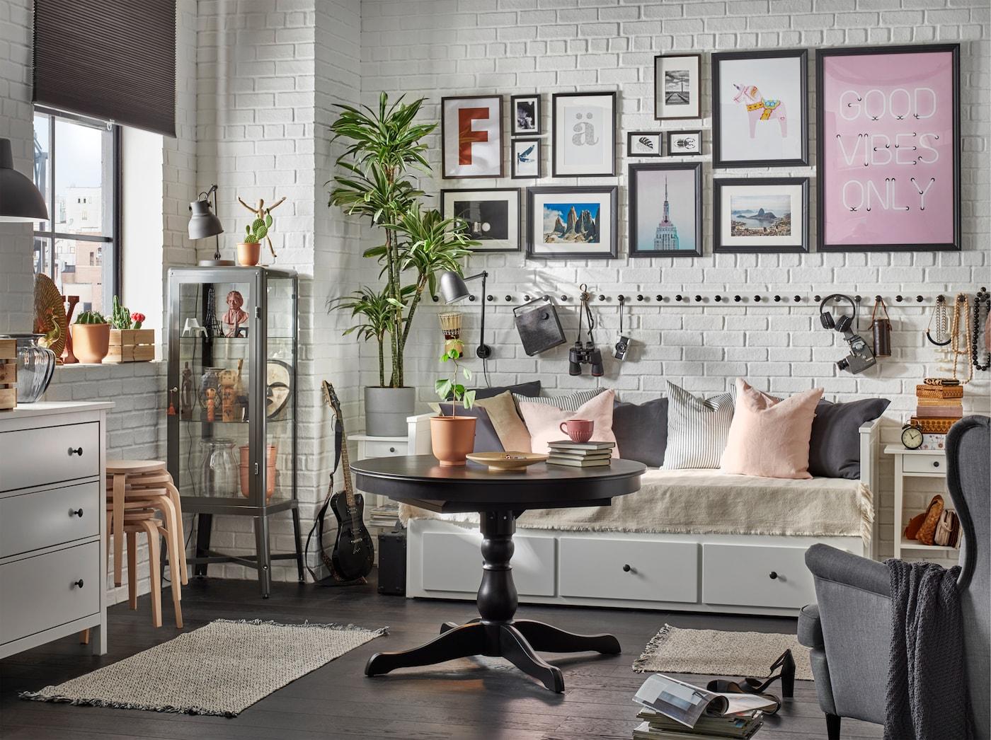 Ein traditionelles Wohn- und Schlafzimmer mit weißer Kommode, Ohrensessel, schwarzem Ausziehtisch, weißem Tagesbett und Teppich.