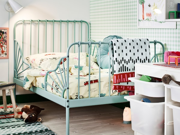 Ein türkisfarbenes MINNEN Bettgestell in der Ecke eines Kinderzimmers. Drumherum sind Spielzeug, eine Leseleuchte und Aufbewahrung zu sehen.