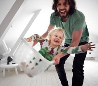 Ein Vater schwingt sein Kind in einem Wäschekorb herum.