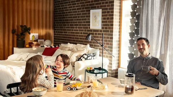 Ein Vater sitzt entspannt am Frühstückstisch und genießt seinen Kaffee, während seine zwei Kinder mit dem Essen spielen.