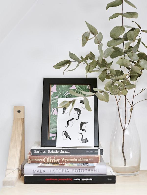 Ein Wandregal mit Büchern, Bildern und einer Vase, u. a. mit EKBY VALTER Konsole Birke.