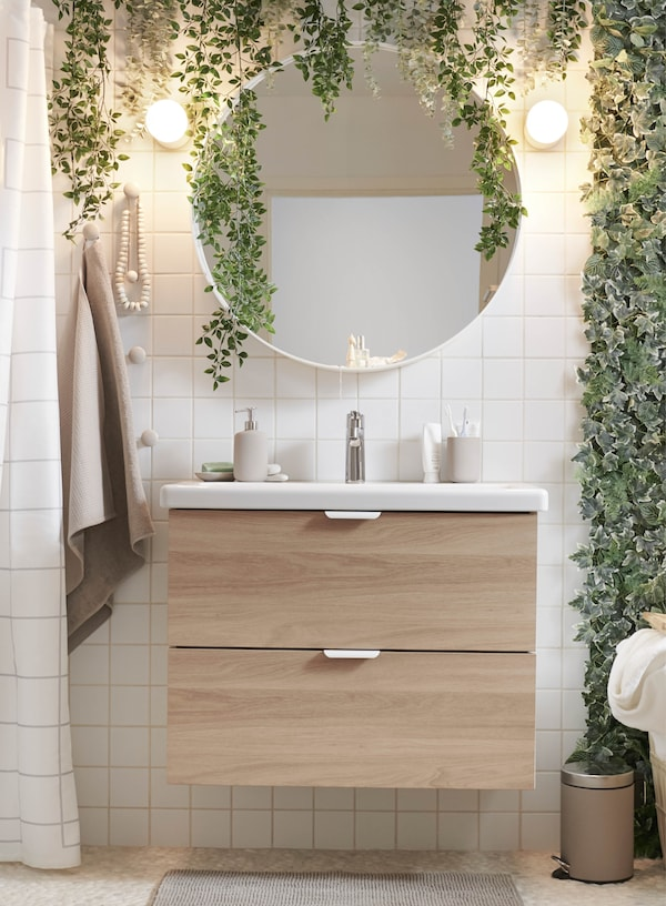 Ein Waschbeckenunterschrank mit hellen Holzfronten unter einem großen runden Spiegel und vielen Pflanzen, die an der Wand befestigt sind.