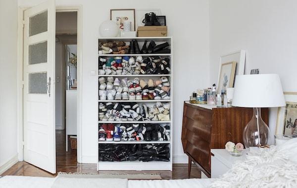 Ein weiß eingerichtetes Schlafzimmer mit Holzböden und Schuhen in einem Bücherregal