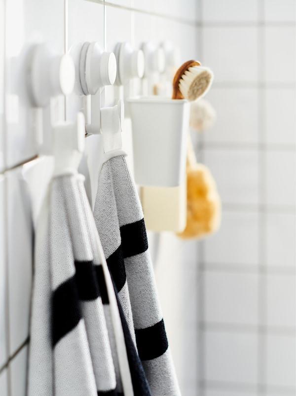 Ein weiss gefliestes Badezimmer mit einer Reihe TISKEN Haken mit Saugnapf, an denen u. a. ein KINNEN Badetuch zu sehen ist.