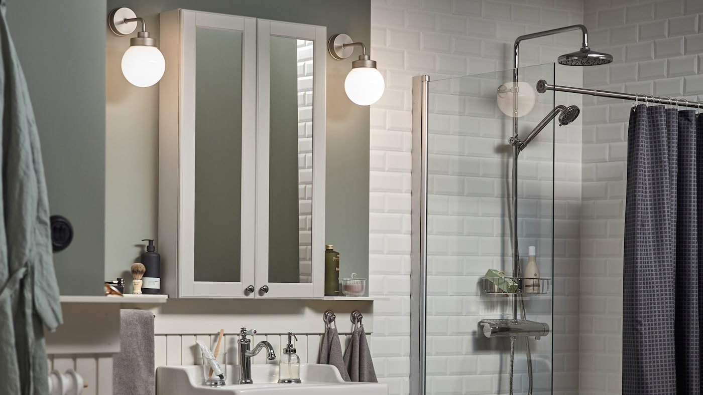 Ein weiß gefliestes Badezimmer mit hellgrünen Wänden und zwei FRIHULT Wandleuchten beidseitig eines GODMORGON Spiegelschrankes.