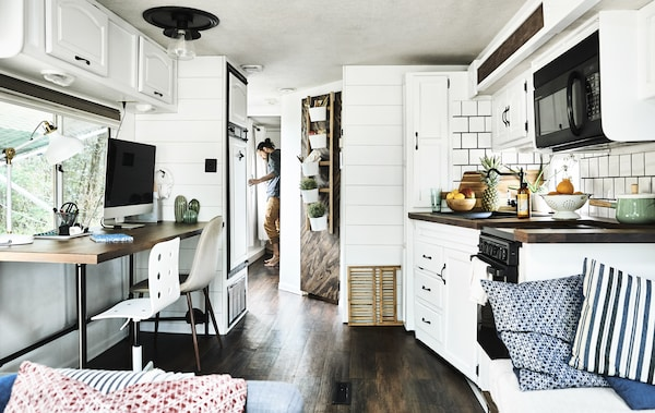 Ein weiß gehaltener Küchen- und Schreibtischbereich, u. a. mit KARLBY Arbeitsplatte Nussbaum. Dahinter steht Karlton am Ausgang des Wohnmobils.