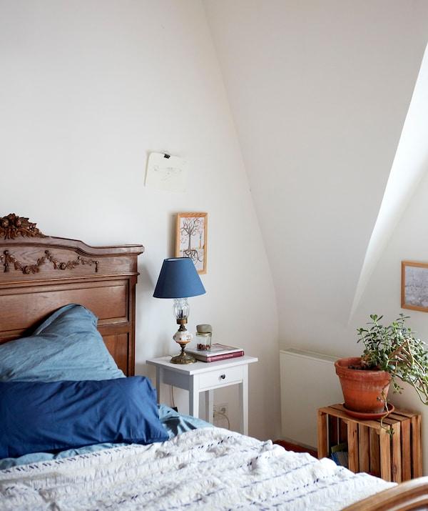 Ein weiss gehaltenes Schlafzimmer mit Dachschräge, einem dunkelbraunen Holzbett und blauer Bettwäsche, u. a. mit HEMNES Ablagetisch in Weiss