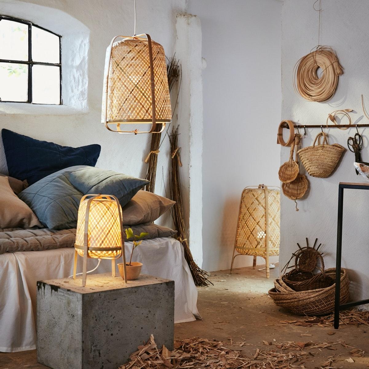 Ein weiß gestalteter Raum mit neutralfarbenen Textilien, Rattankörben und einer KNIXHULT Stand-, Tisch- und Hängeleuchte.