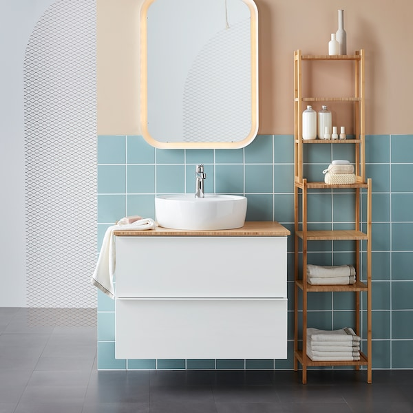 Ein weisser Badezimmerschrank mit einem runden Aufsatzwaschbecken, daneben ein Bambusregal.