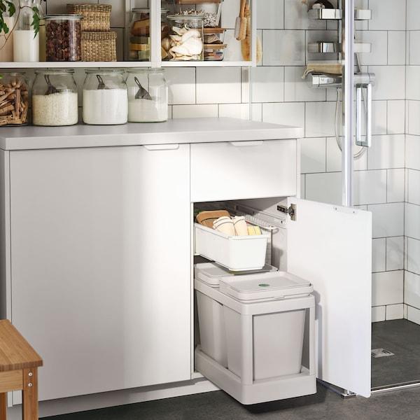 Ein weißer Badezimmerschrank mit eingebauter HALLBAR Abfalltrennungslösung in hellgrau.