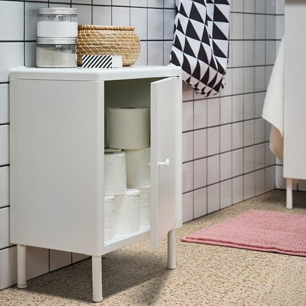 Ein weißer DYNAN Schrank mit Tür, die offen steht und den Blick auf gestapeltes Toilettenpapier freigibt. Oben auf dem Schrank stehen ein Korb mit Deckel und Behälter.