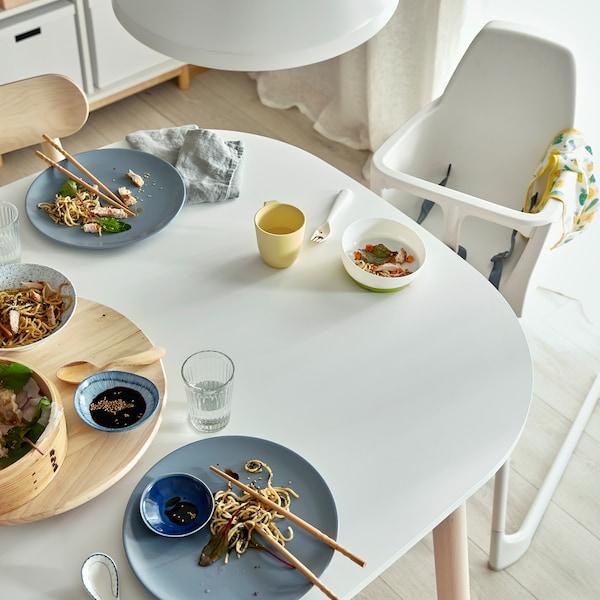 Ein weißer Esstisch mit Resten eines Familienessens. Neben dem Tisch ist ein weißer Hochstuhl zu sehen.
