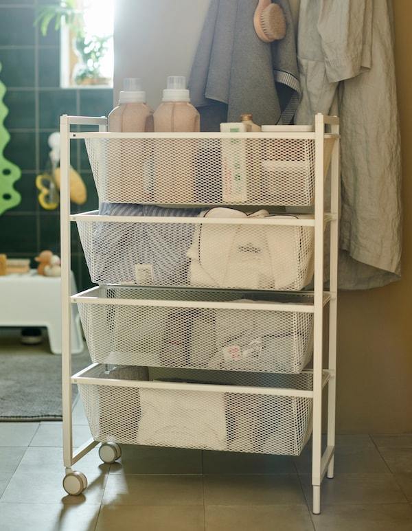 Ein weisser JONAXEL Rahmen mit Netzdrahtkörben und Rollen bewahrt Handtücher, Kleidung und Waschmittel auf.