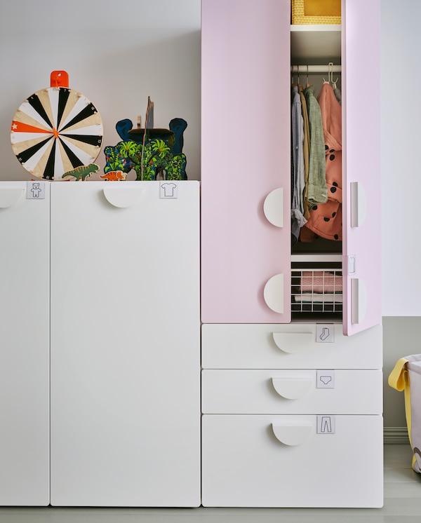 Ein weißer Kleiderschrank mit Auszug und ein Kleiderschrank mit weißen Schubladen und Türen in Blassrosa. Eine Tür steht offen und gibt den Blick auf aufbewahrte Kleidung frei.