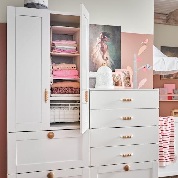 Ein weißer Kleiderschrank mit drei Schubladen und zwei Türen mit Holzgriffen. Eine Tür steht offen und gibt den Blick auf gefaltete Kleidung in Aufbewahrungsfächern frei.