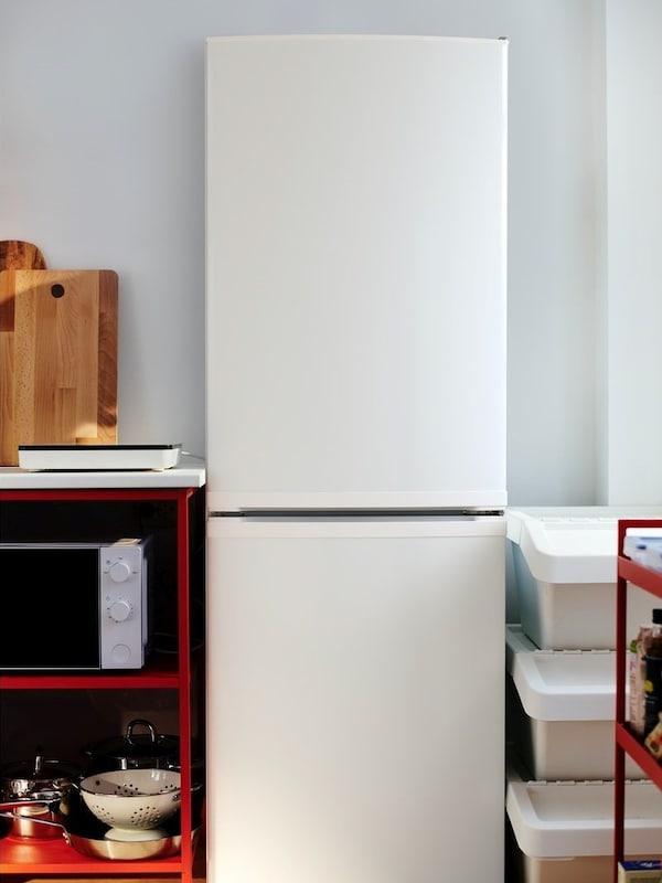 Ein weißer LAGAN Kühl- und Gefrierschrank, steht vor einer weißen Wand. Daneben sind weiße Boxen und ein rotes Regal mit Mikrowelle zu sehen.