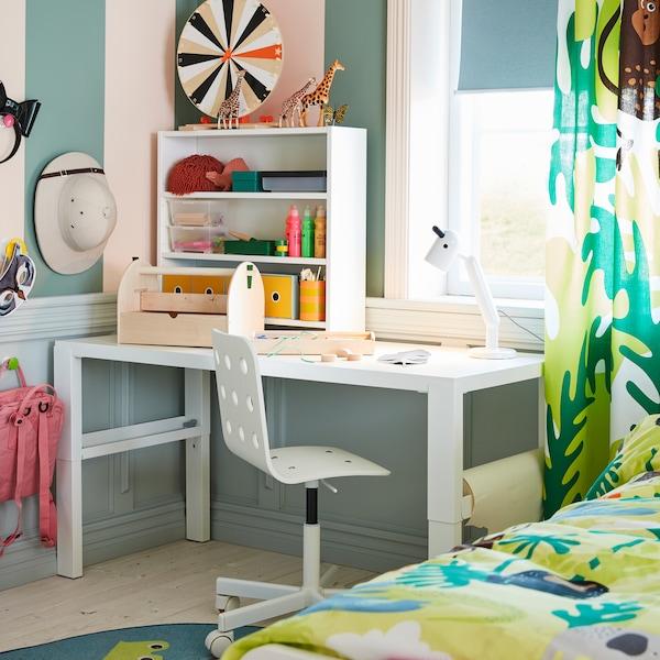 Ein weißer PÅHL Schreibtisch mit Aufsatz am Fenster eines Kinderzimmers. Daneben ist eine Gardine mit Dschungelmuster zu sehen.