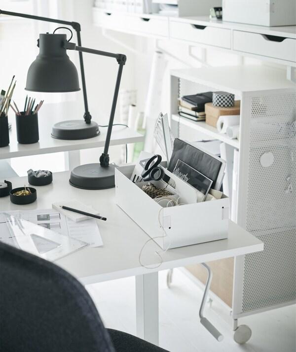 Ein weißer Schreibtisch mit Utensilienorganisation und einer grauen Schreibtischleuchte.