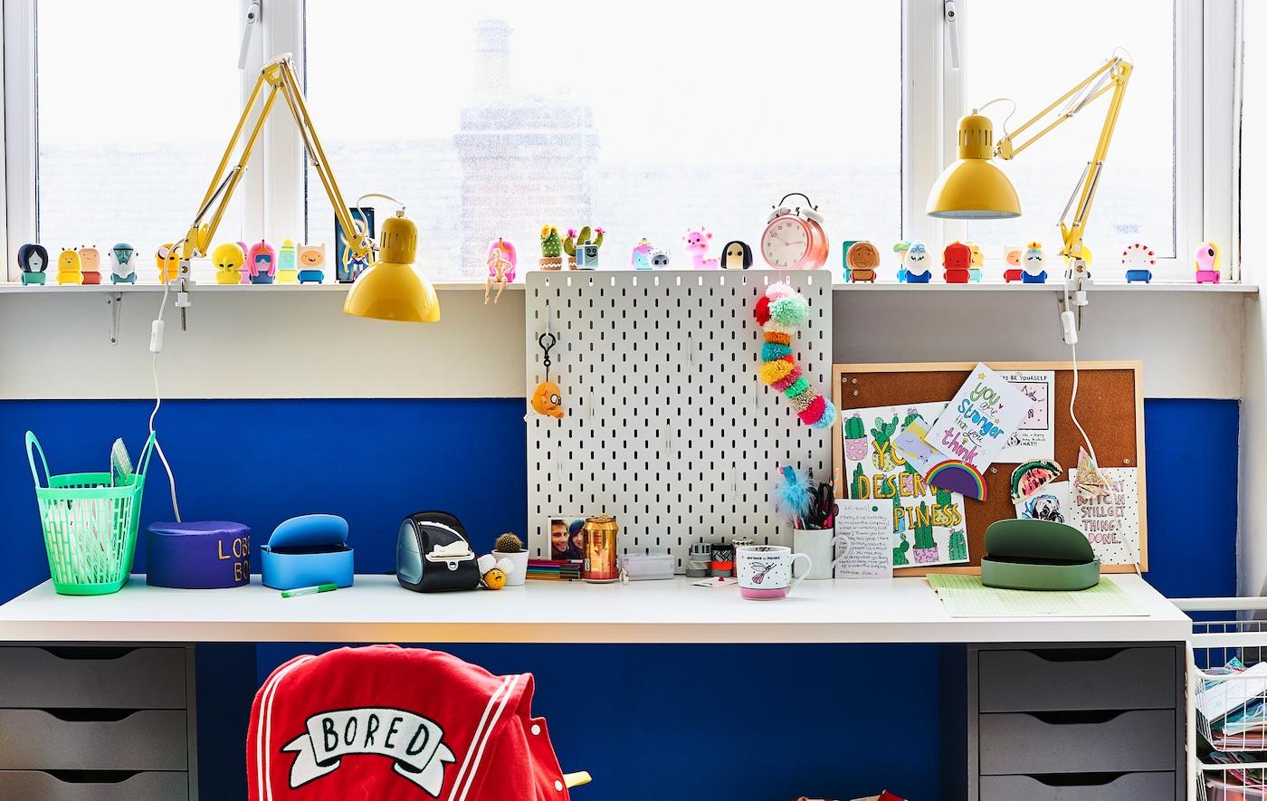 Ein weisser Schreibtisch und gelbe Leuchten vor einer blauen Wand