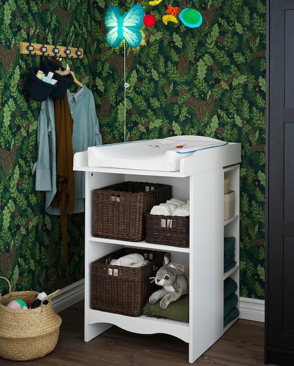 Ein weißer SMÅGÖRA Wickeltisch mit mehreren Ablagen, auf denen Körbe, Windeln und mehr Platz haben.