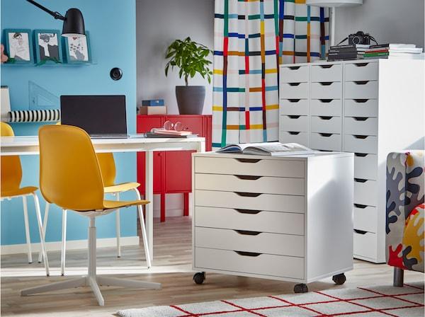 Ein weißer Tisch mit einem LEIFARNE Drehstuhl in Dunkelgelb, daneben ein Schubladenelement auf Rollen.