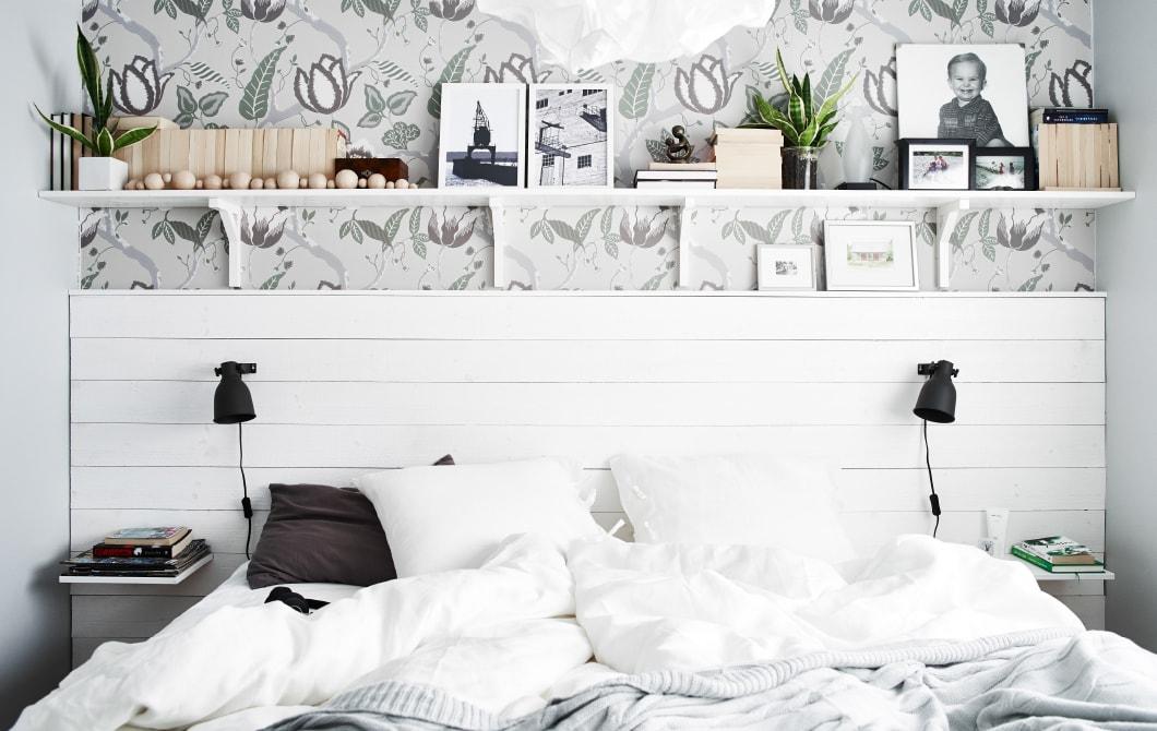 Ein weißes Bett mit weißen Hängeregalen und maritimen Elementen