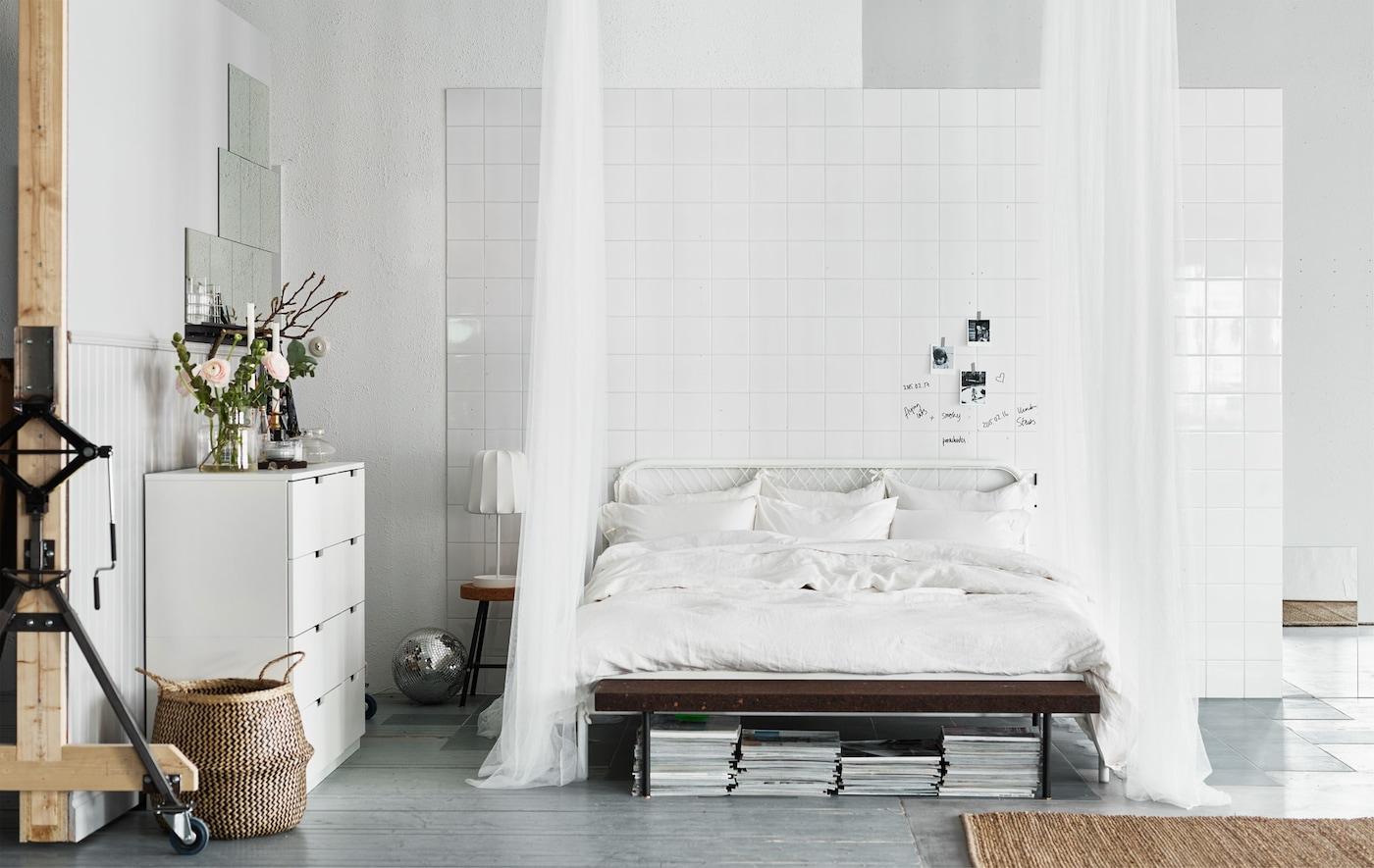 Ein weißes Bett vor einer weißen Fliesenwand mit weißen herabhängenden Stoffen in einem hellen Raum