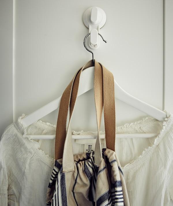 Ein weißes Hemd und eine Tasche an einem Kleiderbügel, der an TISKEN Haken mit Saugnapf in Weiß hängt.