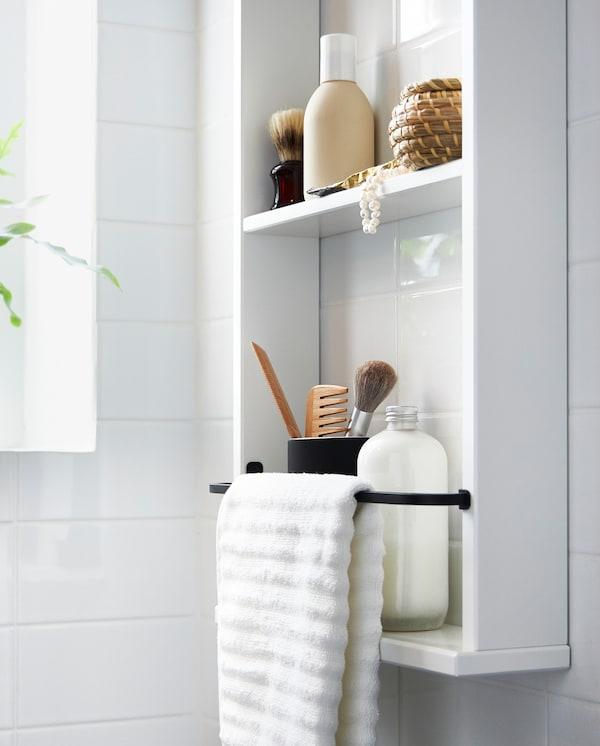 Ein weisses HEMNES Wandregal mit Fläschchen, Make-up und einem weissen Handtuch, das an der schwarzen Stange davor hängt.