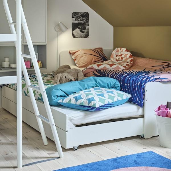 Ein weißes SLÄKT Bettgestell mit Unterbett + Aufbewahrung, bei dem das Unterbett hervorgezogen und zum Übernachten hergerichtet ist. Auf dem Bett ist ein Stofftier zu sehen.