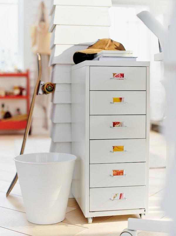 Ein weißes Zimmer, in dem ein HELMER Schubladenelement auf Rollen vor einem getäfelten Holzpfosten steht. An dem Pfosten lehnt ein Skateboard.