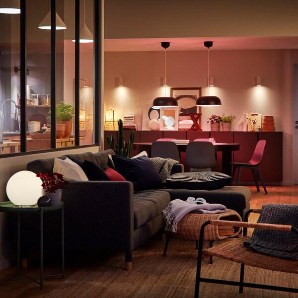Ein Wohnbereich, durch smarte Beleuchtung in Hänge- und Tischleuchten in sanftes Licht getaucht.