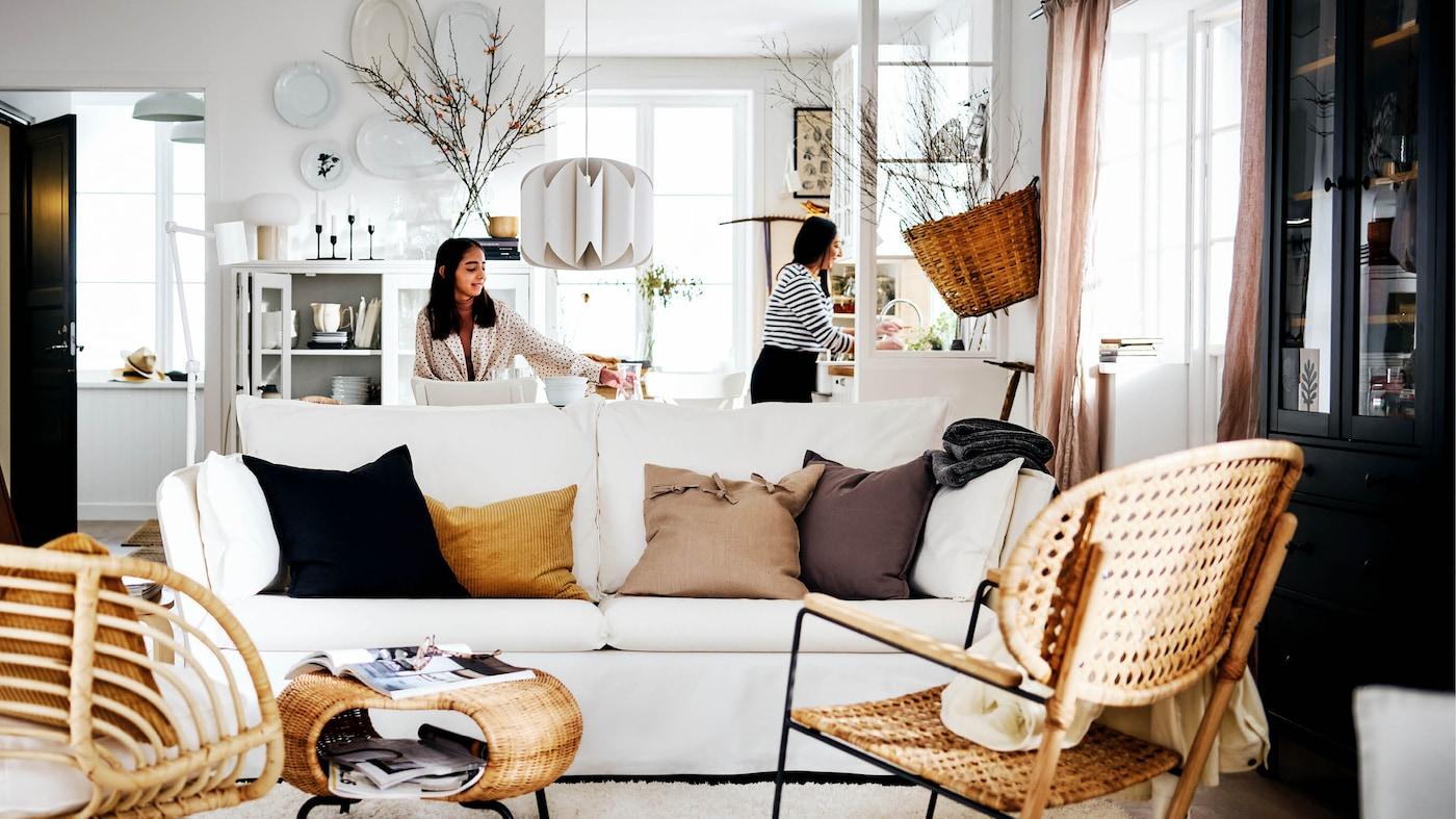 Ein Wohnbereich im Landhausstil. Zwei Frauen stehen hinter einem weißen BACKSÄLEN Sofa, das hinter einem Teppich und zwei Sesseln steht.