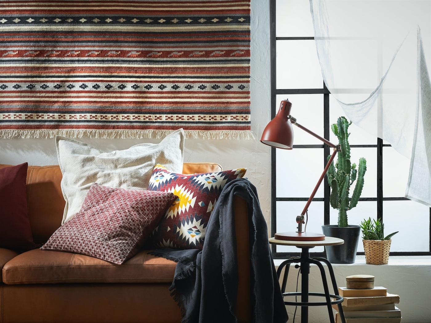 Ein Wohnzimmer eingerichtet im Boho chic Stil mit einem Perserteppich an der Wand, einem einladenden Sofa mir vielen Kissen und Decken.