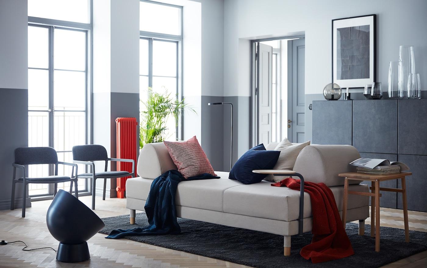 Ein Wohnzimmer In Blau , Grau  Und Rottönen Und Einem Modernen FLOTTEBO  Bettsofa Mit