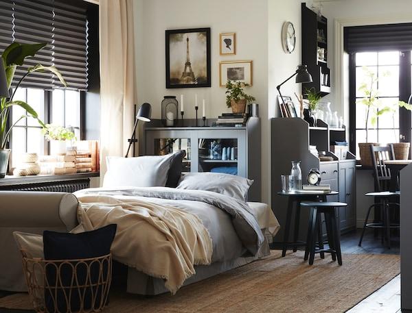 Ein Wohnzimmer, in dem das Bettsofa zum Schlafen vorbereitet ist. In der Nähe stehen eine graue HAUGA Vitrine und graue HAUGA Schränke mit Türen.