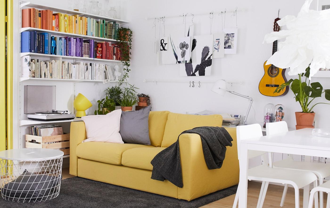 Ein Wohnzimmer in Weiss, dekoriert mit Akzentfarben an den Wänden und am Esstisch.