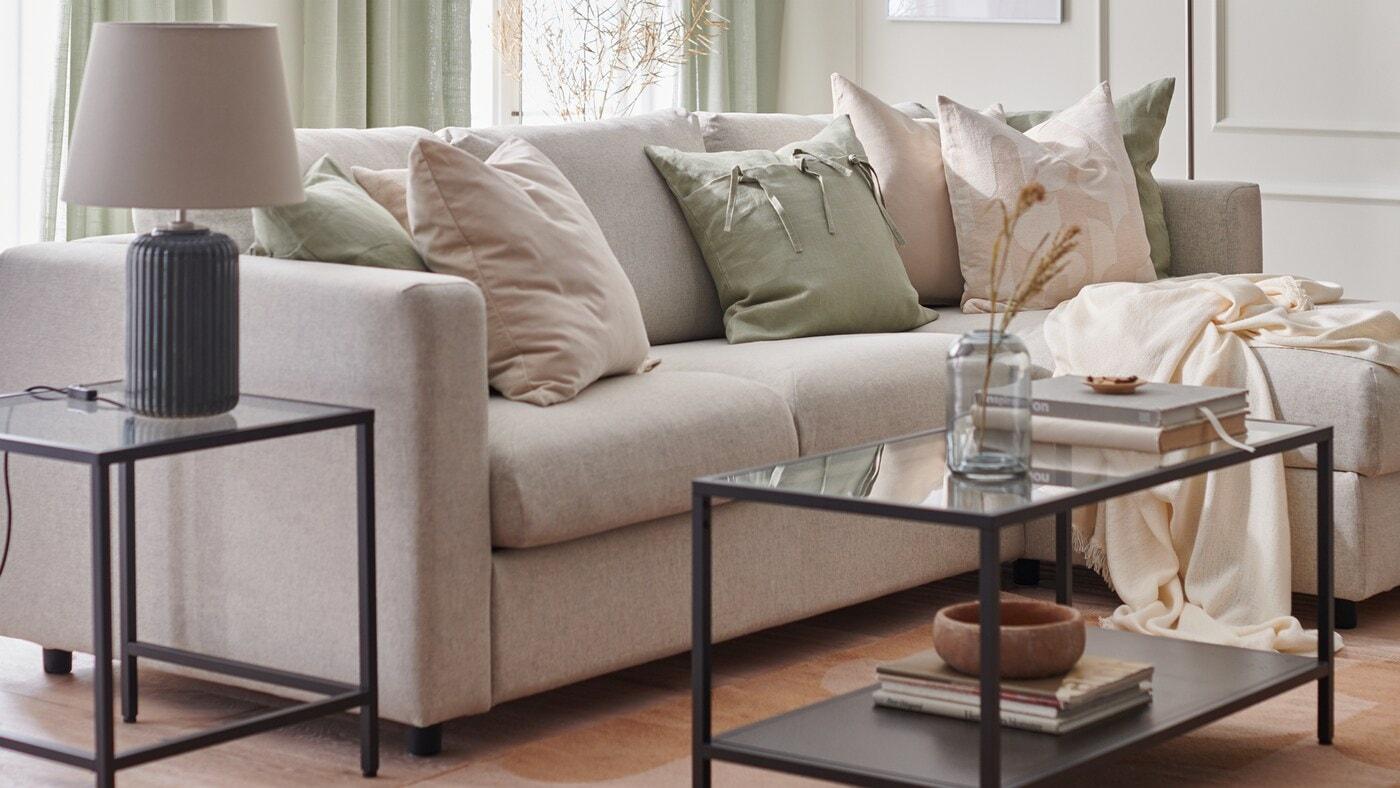 Ein Wohnzimmer ist für den Frühling eingerichtet mit einem VIMLE 3er-Sofa, Kissen in RÖDASK Kissenbezügen in Beige und einer SNÖBYAR Tischleuchte auf einem VITTSJÖ Beistelltisch.