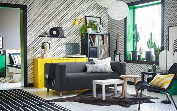"""Ein Wohnzimmer mit diagonal gestreiften Wänden und KLIPPAN 2er-Sofa mit Bezug """"Avsiktlig"""" in Weiß/Schwarz"""