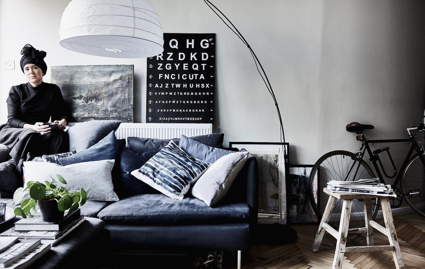 Ein Wohnzimmer mit dunklem Sofa und jeder Menge Kissen