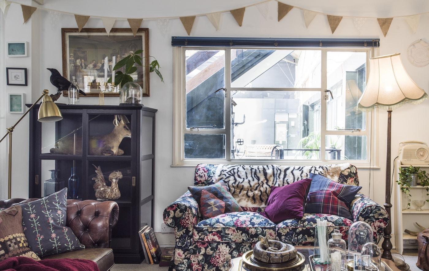 """Ein Wohnzimmer mit einem EKTORP 2er-Sofa mit Bezug """"Lingbo"""" in Bunt, Vitrinen und vielen Leuchten."""