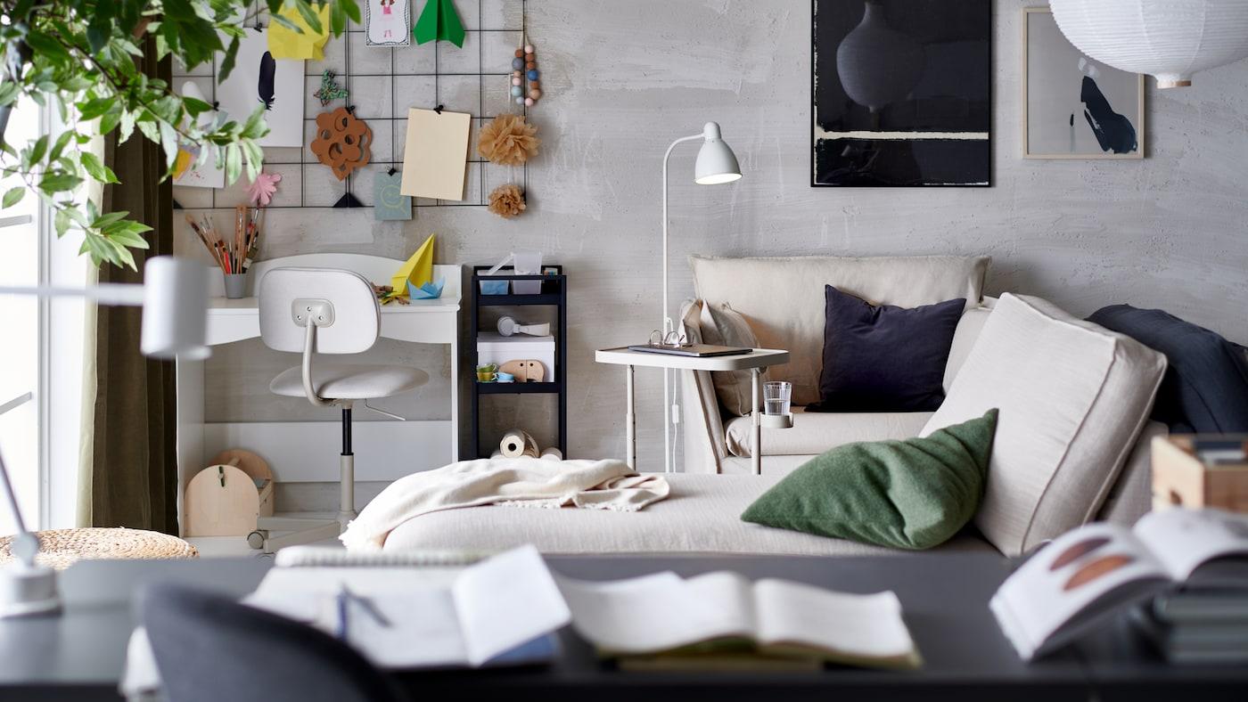 Ein Wohnzimmer mit einem kleinen Arbeitsplatz in einer Ecke, u. a. mit einem Laptoptisch neben einem Sessel, Kissen und einer Récamiere.