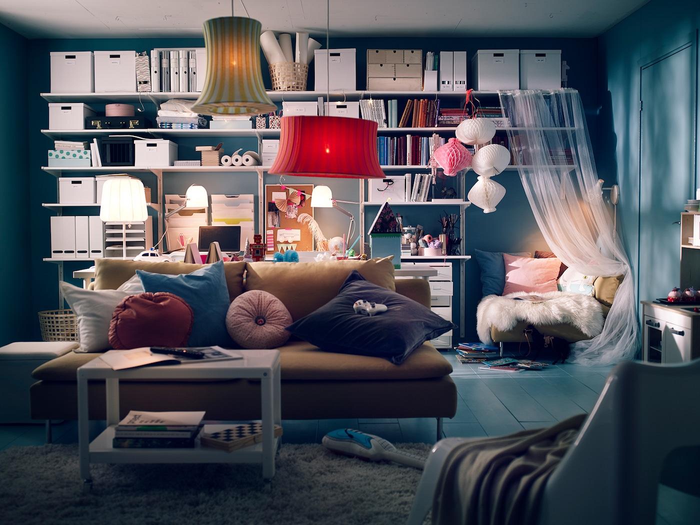 Ein Wohnzimmer mit einem Sofa, hinter dem ein Schreibtisch & ein großes Regalsystem steht.