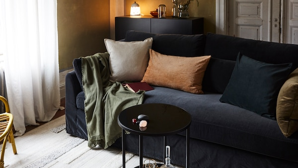 Ein Wohnzimmer mit einem Sofa, Kissen, einem Plaid, einem Teppich, einem kleinen Couchtisch, einem Sideboard mit einer Leuchte und Vasen darauf und ein Sessel aus Rattan.