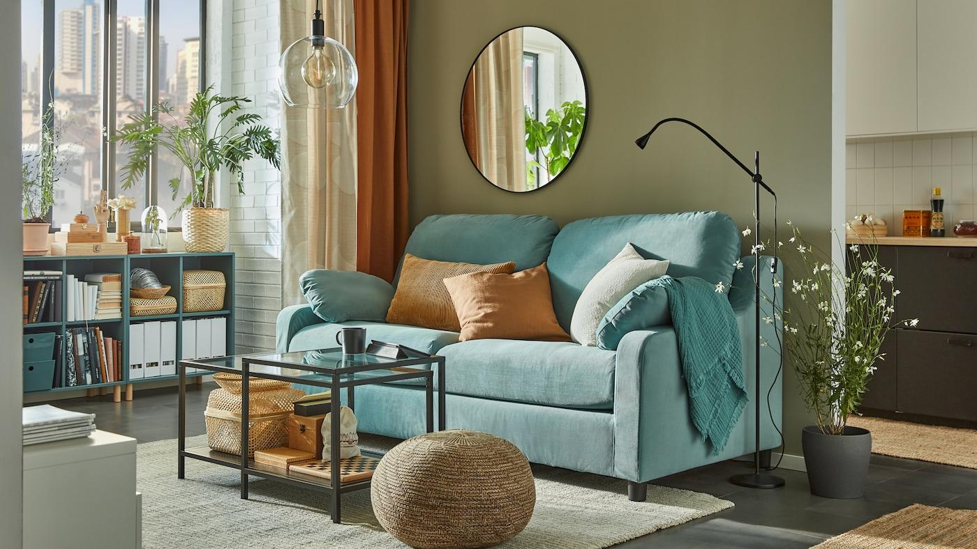 Ein Wohnzimmer mit einem türkisfarbenen Sofa mit beigen und braunen Kissen vor einer beigen Wand, an der ein großer runder Spiegel hängt.