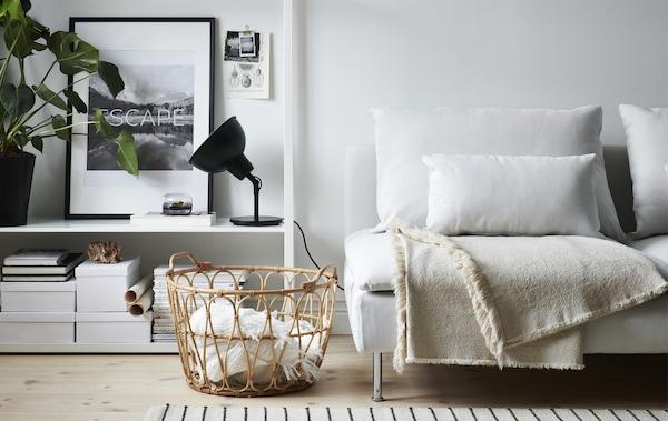 ein wohnzimmer mit einem weien sofa einer schwarzen leuchte offener aufbewahrung und weidenkrben voller